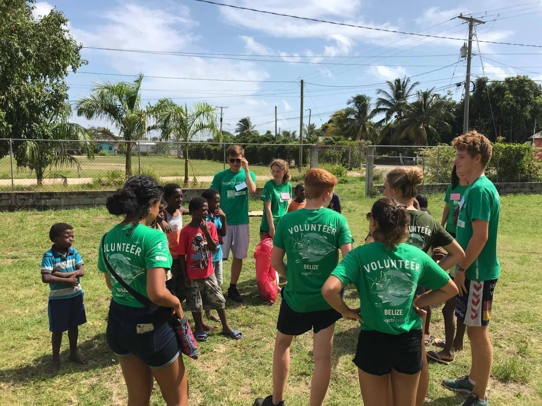 High school students volunteering in Belize explain a litter and recycling awareness activity to children at a summer camp